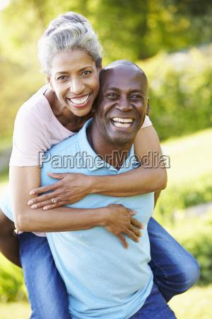 mature man giving woman piggyback in