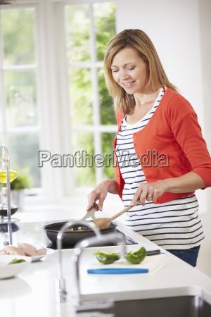 woman standing at hob preparing meal