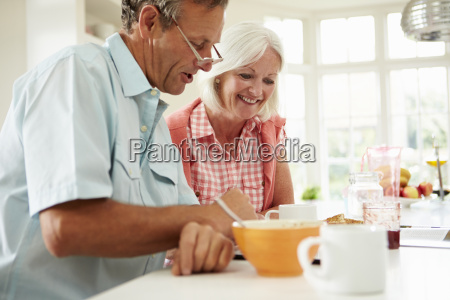 middle aged couple looking at digital