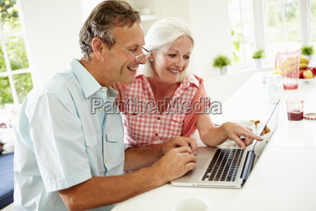 middle aged couple looking at laptop