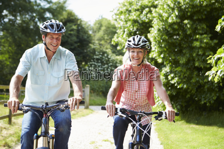 middle aged couple enjoying country cycle