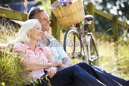 middle aged couple relaxing on country
