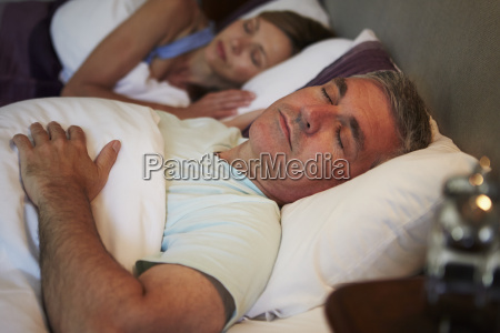 middle aged couple asleep in bed