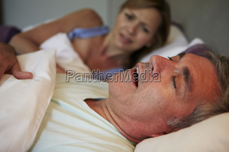 man keeping woman awake in bed