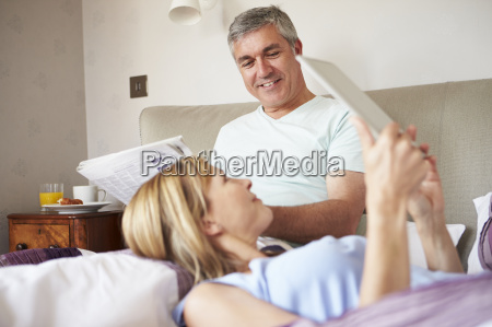 couple relaxing in bed with newspaper