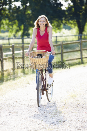 attractive woman riding bike along country