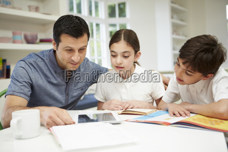 father helping children with homework using