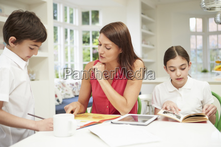 mother helping children with homework using