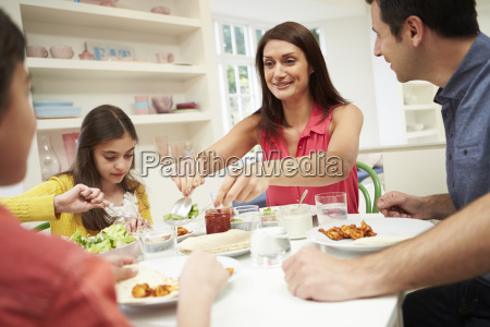 hispanic family sitting at table eating