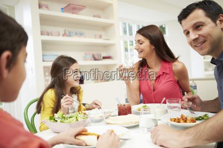 hispanic family sitting at table eating