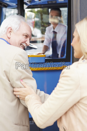 woman helping senior man to board