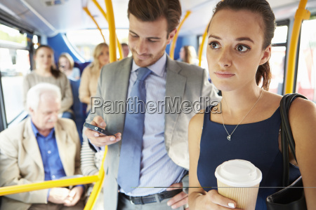 passagiere standing on busy commuter bus