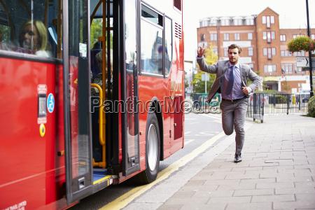 geschaeftsmann laeuft um bus zu stoppen