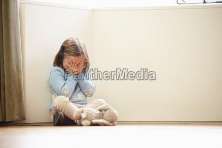 unglueckliches kind sitzen auf boden in