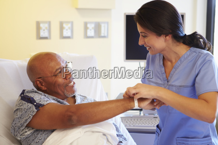 nurse putting wristband on senior male
