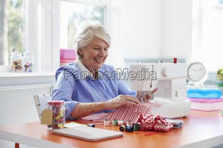senior woman making clothes using sewing