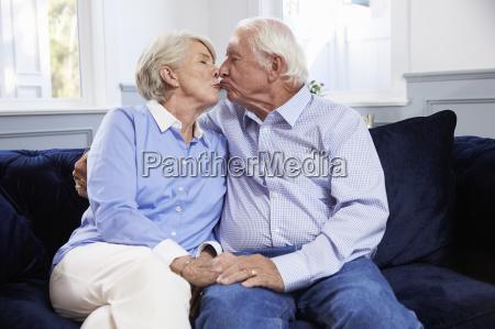 zaertlich senior paar sitzen auf sofa