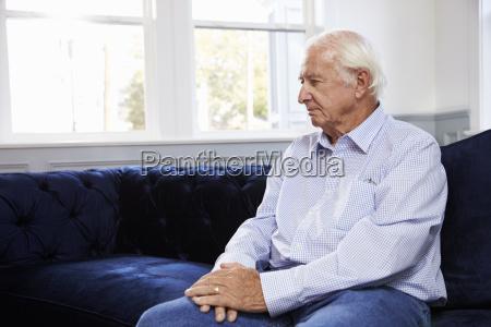 depressed senior man sitting on sofa