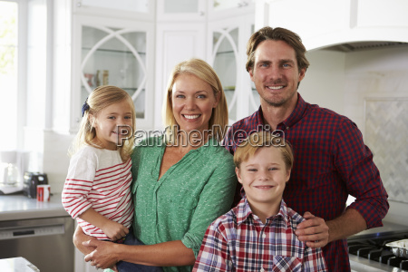 portrait of family standing in kitchen
