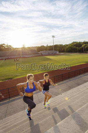 two athlete women running up on