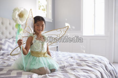 girl dressed in fairy costume sitting