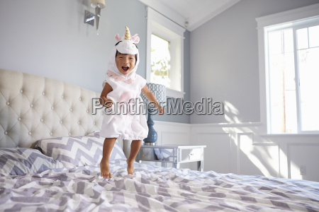 girl dressed in unicorn costume jumping