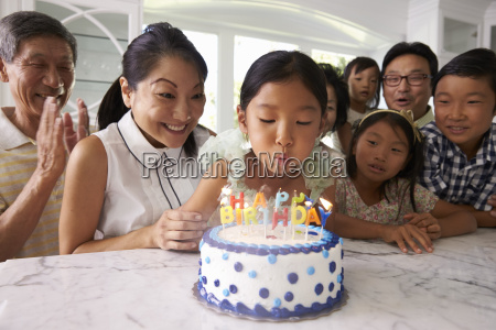 girl blows out candles at family