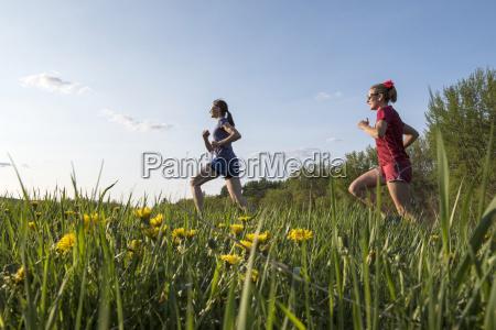 two female runners running on grassy