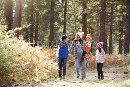 asian mother with three children walking