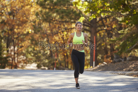 caucasian woman jogging on country road
