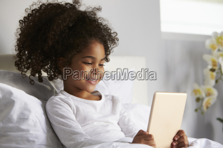 smiling young girl using digital tablet