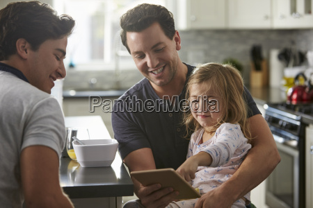 male gay dads use tablet with