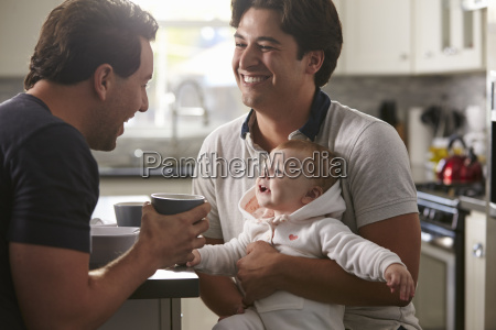 male gay couple holding baby girl