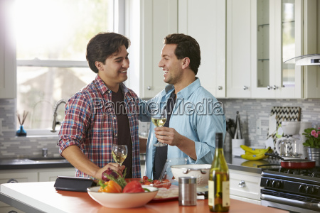 laughing male gay couple drinking wine