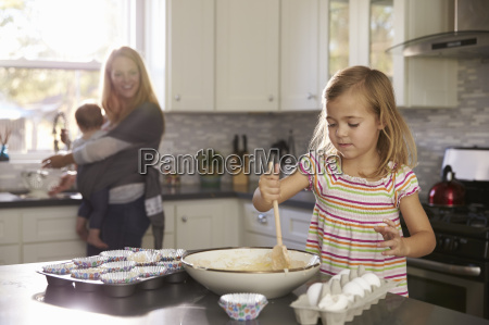 young girl prepares cake mix mum