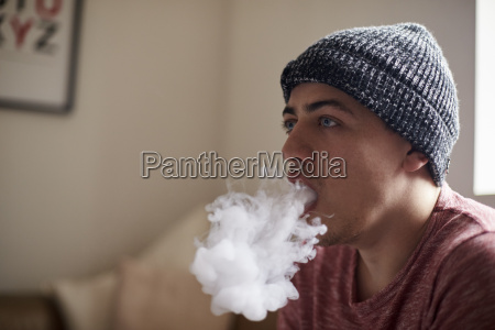 young man exhaling whilst using vapourizer