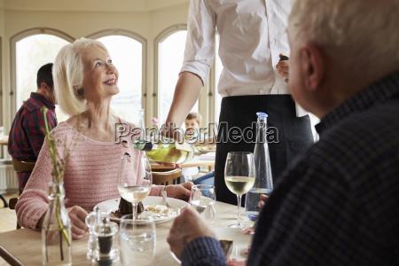 waiter serving wine to senior couple