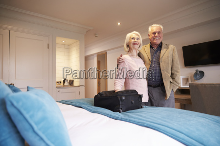 senior couple arriving in hotel room