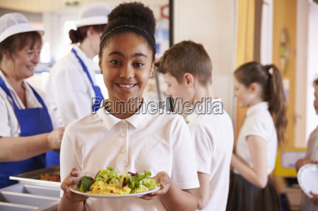 black schoolgirl holds a plate of