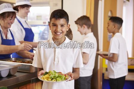 hispanic schoolboy haelt einen teller mit