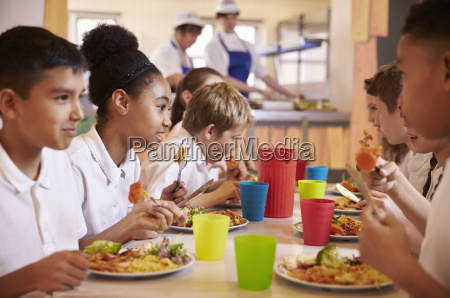 primary school kids eat lunch in