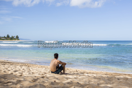 young man sits on the beach