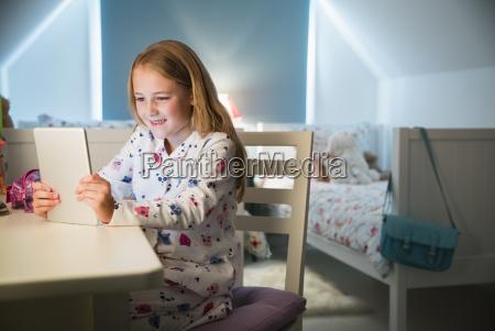 maedchen in pyjamas mit digitalen tablet