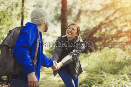 smiling couple holding hands hiking in