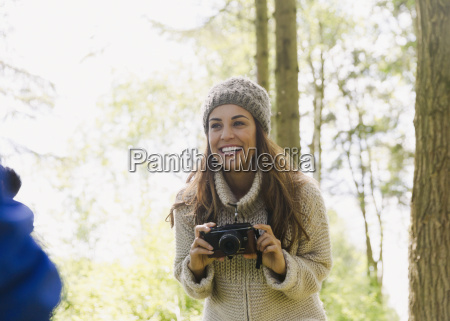 smiling woman using camera in woods
