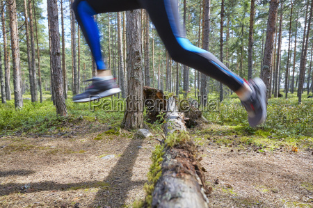 runner jumping over fallen log on