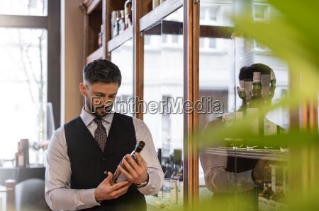 well dressed bartender examining whiskey bottle