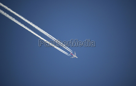 airplane and contrails against blue sky