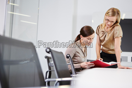 businesswomen sitting at conference table looking