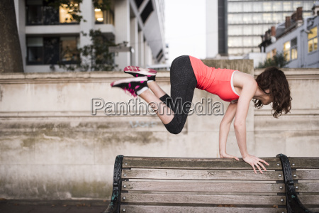 young woman leaping over park bench